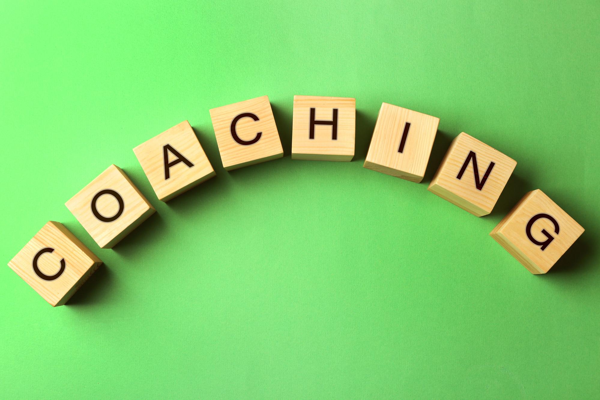 Cubes en bois disposés en arc de cercle, formant le mot coaching, sur fond vert