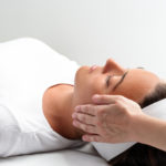 Thérapeute énergéticienne et hypnothérapeute donnant une séance de reiki